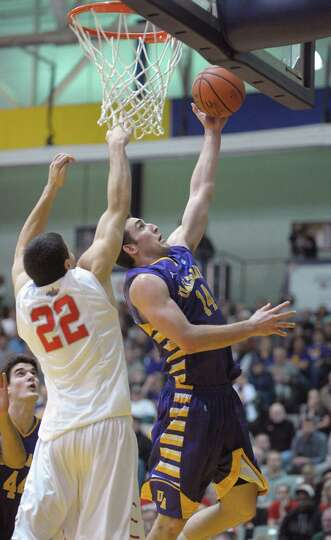 Sam Rowley of UAlbany, right, goes up for a basket around Eric McAlister of Stony Brook during their