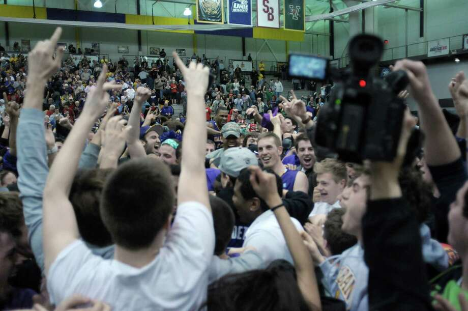 UAlbany fans and players celebrate their win over Stony Brook  at the SEFCU Arena on Sunday, March 10, 2013 in Albany, NY.  (Paul Buckowski / Times Union) Photo: Paul Buckowski