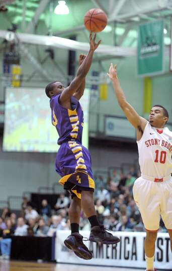 D.J. Evans of UAlbany, left, puts up a shot over Carson Puriefoy of Stony Brook during their game at