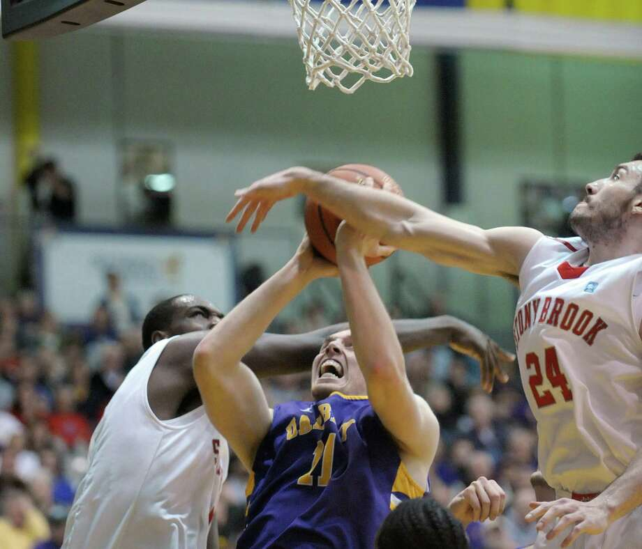 Luke Devlin of UAlbany, center, goes up for a basket through two Stony Brook defenders during their game at the SEFCU Arena on Sunday, March 10, 2013 in Albany, NY.  (Paul Buckowski / Times Union) Photo: Paul Buckowski