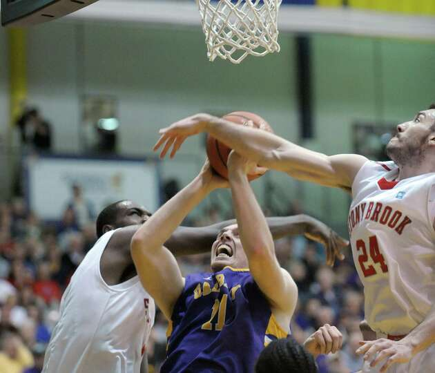 Luke Devlin of UAlbany, center, goes up for a basket through two Stony Brook defenders during their