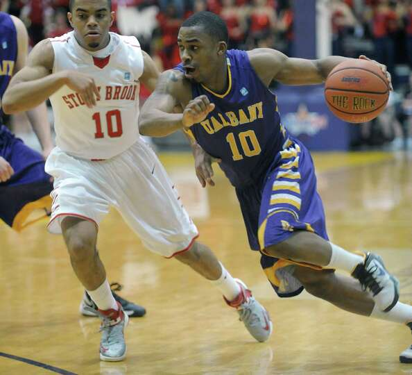 Mike Black of UAlbany, right, drives past Carson Puriefoy of Stony Brook during their game at the SE