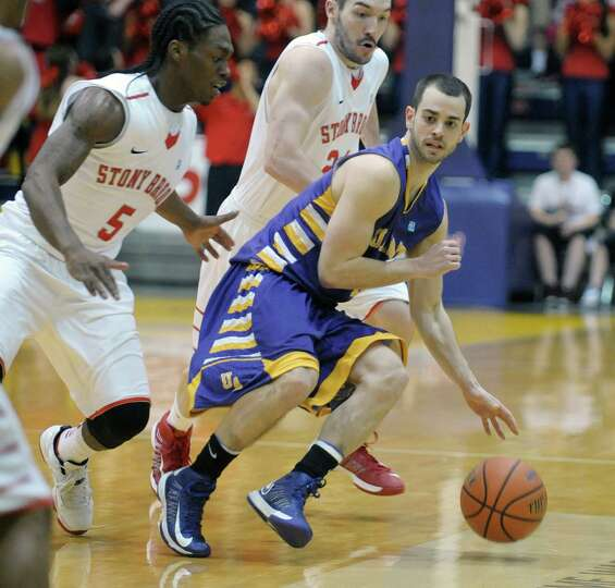 Jacob Lati of UAlbany brings the ball up the court late in the game as Stony Brook players try for t