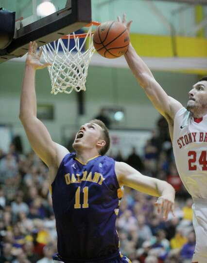 Luke Devlin of UAlbany, left, is fouled by Tommy Brenton of Stony Brook late in the game   at the SE