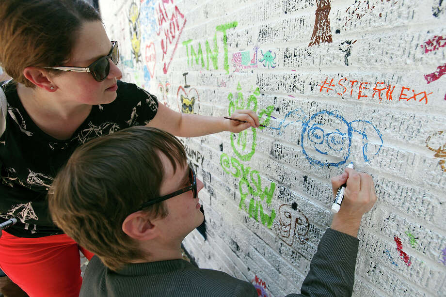 Quirine Hartong (left) and Neil Voss draw their daughter Anora Voss on the HGTV ÒArt on the SideÓ wall near the Austin Convention Center during South by Southwest Sunday March 10, 2013 in Austin, TX. Photo: Edward A. Ornelas, San Antonio Express-News / © 2013 San Antonio Express-News
