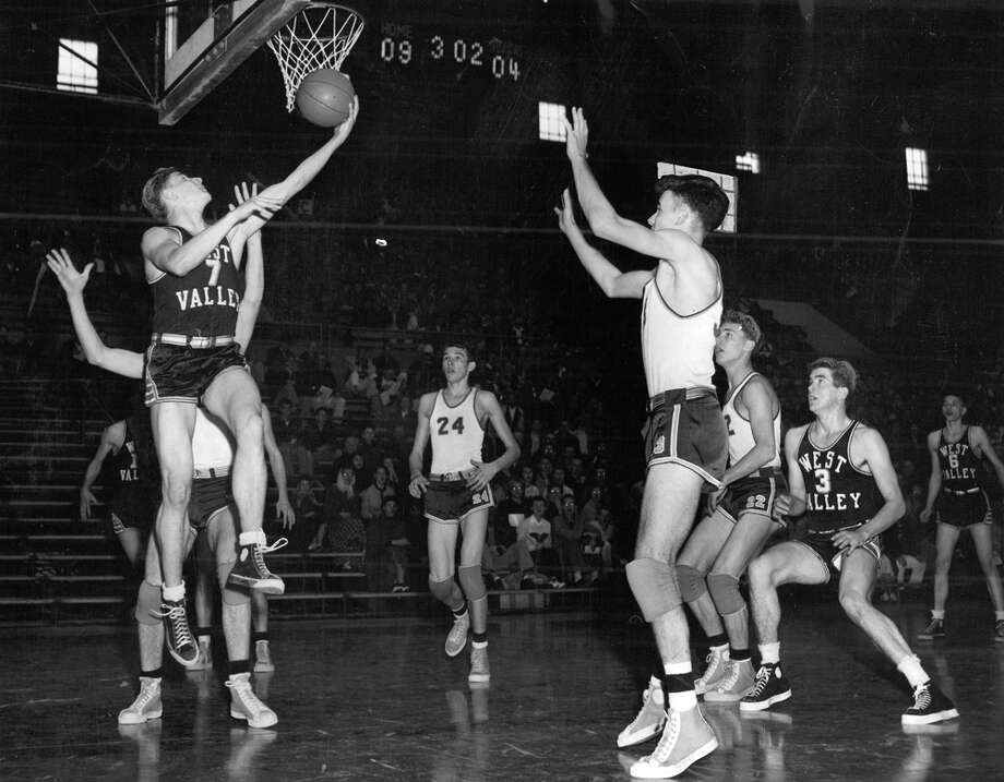 "The caption for this March 1953 photo read: ""West Valley's Ed Luedtke (7) tries for a jumping backhand shot in opening game of the State High School Basketball Tournament at UW Pavilion against White River. Other players include White River's Don Kovacevich (24), Harold Hickenbottom (third from right) and Don Blakely. At right is O'Brien (3), West Valley."" Photo: Seattlepi.com File"