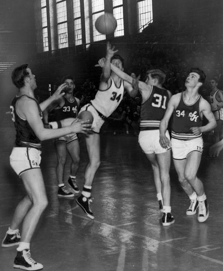 "This March 1951 photo caption read: ""Bell Medin of Ballard goes in for an underhand shot and is fouled by Jim Van Zee (31) of South Kitsap. Others are South Kitsap players Bob Gehring (left); Cliff Payseno (behind Medin) and Ray Wagner (34). Ballard won the game and remained in (the) tournament."" Photo: Seattlepi.com File"