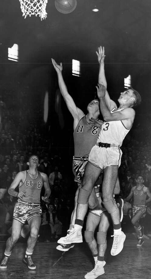 "This March 1954 photo caption read: ""Don Marler, Wapato guard (No. 3) goes up for a one-handed push shot against Everett in the opening game of the State High School Basketball Tournament Wednesday. In on the play are Everettt's Pete Cupic (66) and team captain Bill Wilkerson (11). Wapato won 56-42."" Photo: Ken Harris/seattlepi.com File"