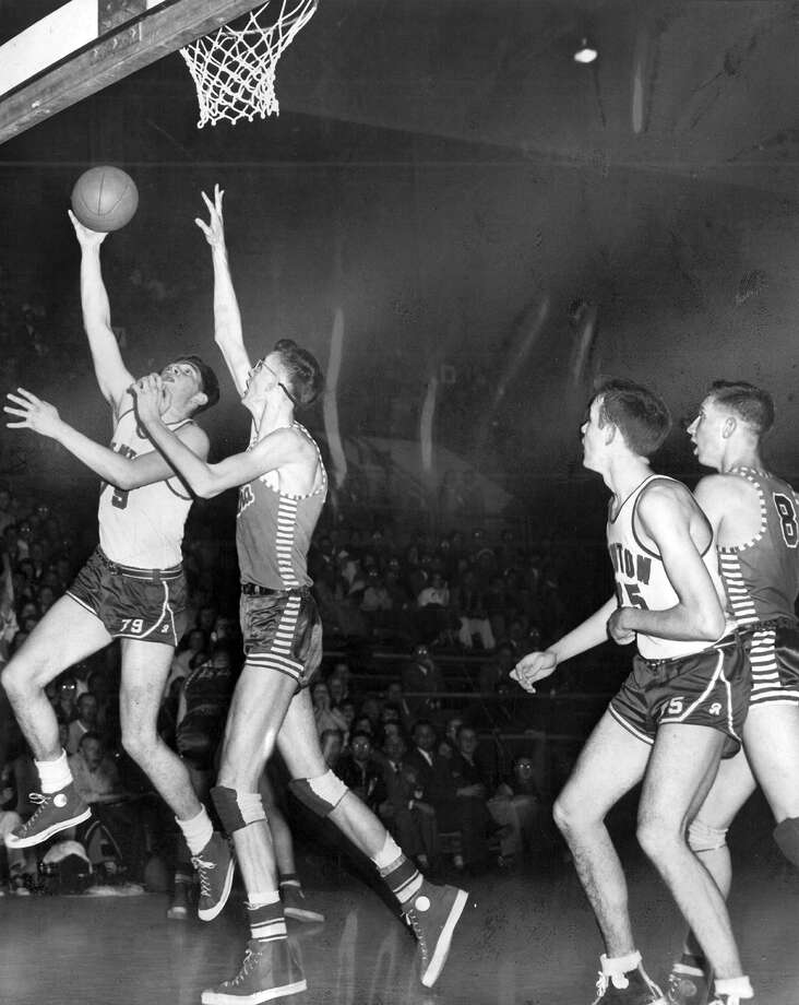 """The caption for this March 13, 1953 photo read: """"Renton's George Strugar, powerful center, evades interference from Elma's Gary Nelson to pop in a field goal as Renton upset pre-tourney favorite Elma, 34-40. Others in this action photo in the state Class A tournament at the Pavilion are Keith Tonkin (75) of Renton, and Wendell Weld (8) of Elma."""" Photo: Ed Watton/seattlepi.com File"""