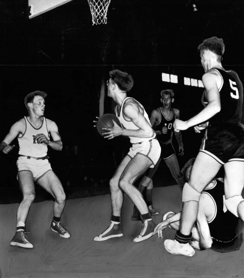 "This March 1954 photo caption read: ""St. Patrick's Jim O'Rourke (No. 14 with ball) draws a bead on the basket in the first half of St. Pat's game with Zillah in the Class B basketball tournament Friday. O'Rourke made the shot. St. Patrick's No. 10 is Jerry Anhorn. Zillah players are Chuck Miszeteer (10), Dave Schmidt (5) and on the floor is Bob Lagenvall. St. Pat's won, 57-55."" Photo: Seattlepi.com File"