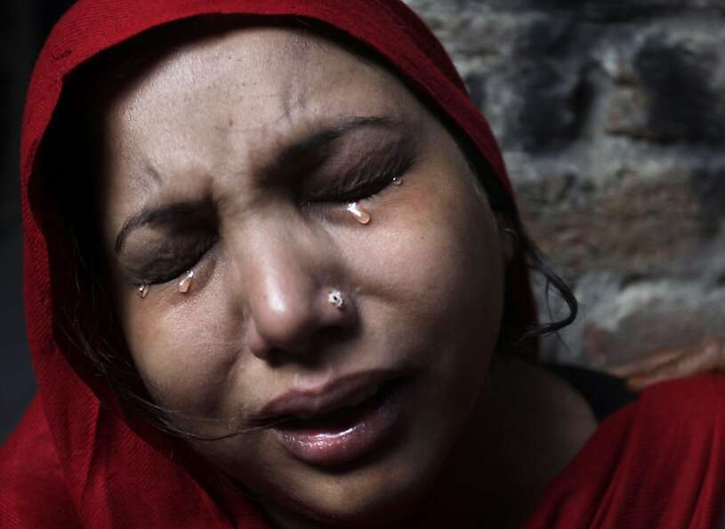 A Pakistani Christian woman weeps after visiting  her home which was damaged by an angry Muslim mob