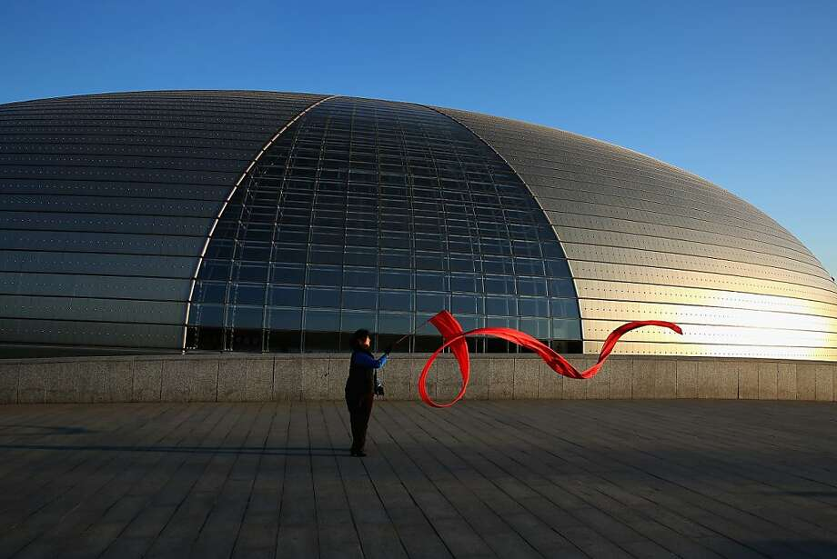 A Chinese woman waves a red ribbon to exercise outside China's National Grand Theater before a plenary session of the National People's Congress on March 10, 2013 in Beijing, China. The State Council, China's cabinet, will begin its seventh restructuring attempt in the past three decades to roll back red tape and reduce administrative intervention. Several departments under the State Council will be reorganized according to a plan on the institutional restructuring and functional transformation of the State Council, which was submitted to the plenary session of the National People's Congress Sunday.  Photo: Feng Li, Getty Images