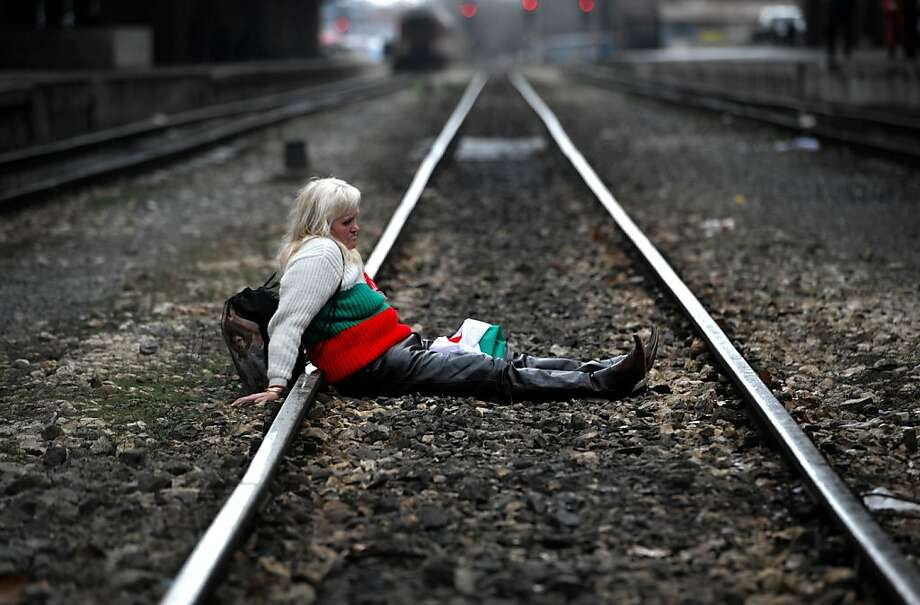 A protester sits on the tracks during a blockade of the railway next to Sofia Central railway station as part of anti-monopoly protest in Sofia on March 10, 2013. Hundreds of Bulgarians joined new rallies across the country on Sunday to protest against poverty and corruption and denounce the whole political establishment.  Photo: Nikolay Doychinov, AFP/Getty Images