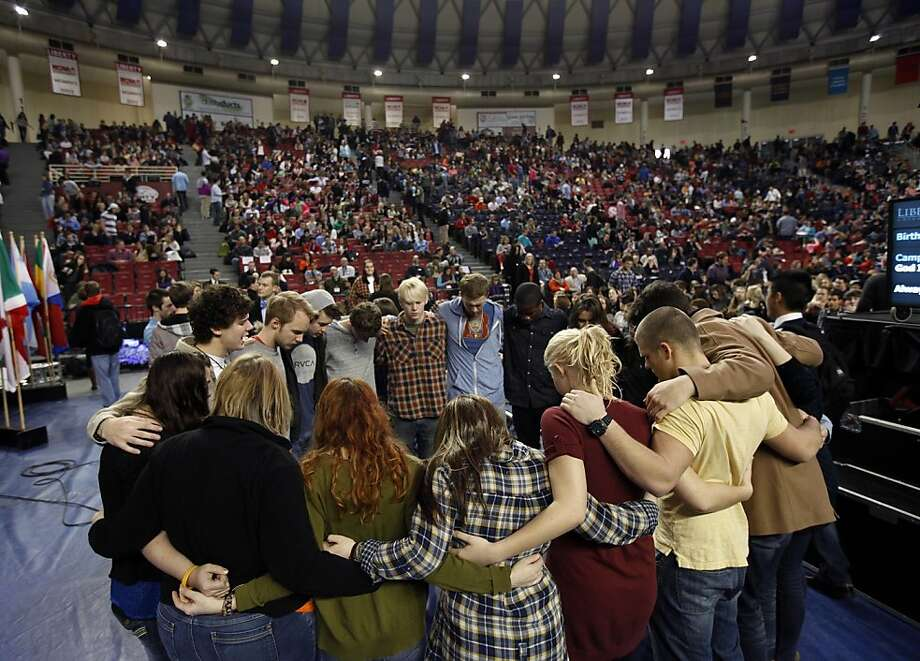 A group of students gather and pray before convocation starts at Liberty University in Lynchburg, Va. Liberty, the small Baptist college that television preacher Jerry Falwell founded in 1971, has capitalized on the online education boom to become an evangelical mega-university with global reach.  Photo: Norm Shafer, Associated Press