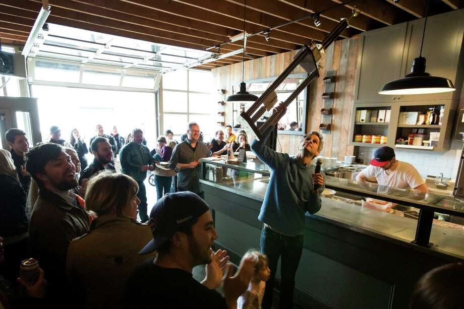 "Marty Penner, hoists one of the many trophies given out to contestants and onlookers during the ""Toss Like a Boss"" event Sunday at the Ballard Pizza Co. in Seattle. The event raised $1,107.97 dollars  for Child Haven. Photo: JORDAN STEAD / SEATTLEPI.COM"
