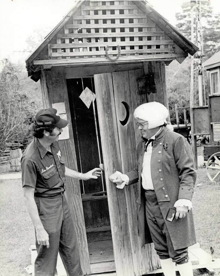 Helicopter pilot James Overstreet and J.W. Shaw, co-chairman of the Nederland Heritage Festival in 1976, inspect an outhouse airlifted from Woodville to Nederland, a highlight of the festival that year. Photo: Archive Photo