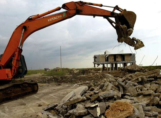 A Hitachi Excavator picks up pieces of concrete and debris of the parking lot and sidewalks near the Welcome Center. The state of Texas is tearing down the Sea Rim State Park Welcome Center that was heavily damaged by Hurricane Rita, never fully repaired, before it took a major blow from Hurricane Ike last year. The center will be rebuilt, but it will take about four years to complete. Dave Ryan/The Enterprise / Beaumont