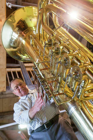Musical instrument craftsman Manfred Paulus adjusts the valves of world's largest functional tuba at the Musikinstrumenten-Museum on March 8, 2013 in Markneukirchen, Germany. Photo: Joern Haufe, Getty Images / 2013 Getty Images