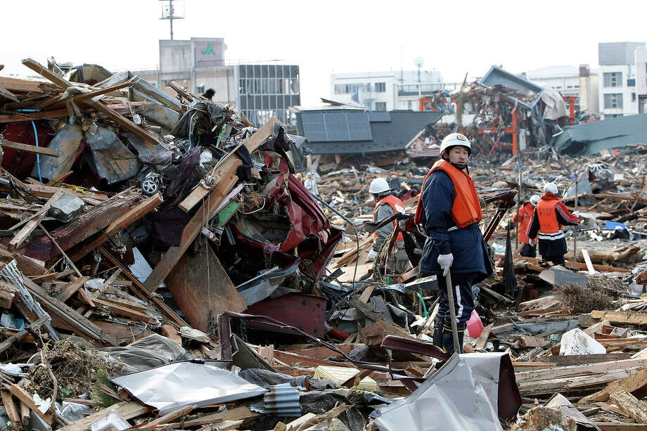 Volunteer firefighters search for victims of Friday's tsunami at Rikuzentakada, Iwate Prefecture, northern Japan, Sunday, March 13, 2011. (AP Photo/Shizuo Kambayashi) Photo: Shizuo Kambayashi, ASSOCIATED PRESS / AP2011