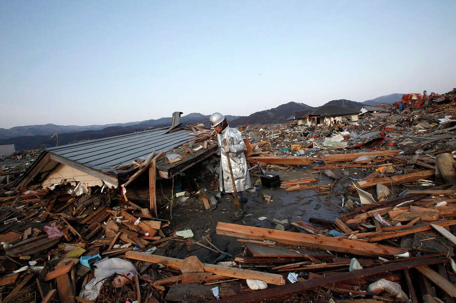 A volunteer firefighter searches for victims of Friday's tsunami at Rikuzentakada, Iwate Prefecture, northern Japan, Sunday, March 13, 2011. (AP Photo/Shizuo Kambayashi) Photo: Shizuo Kambayashi, ASSOCIATED PRESS / AP2011