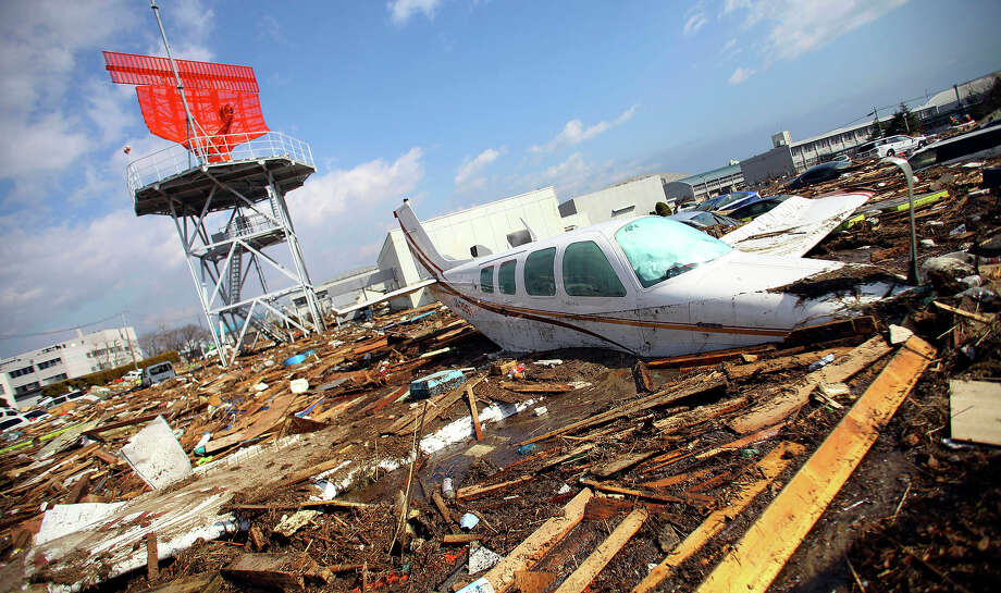 A light plane mingles with debris  following a massive Tsunami triggered by a huge earthquake at Sendai airport in  Sendai, northern Japan,  Saturday, March 12, 2011.(AP Photo/Junji Kurokawa) Photo: Junji Kurokawa, ASSOCIATED PRESS / AP2011