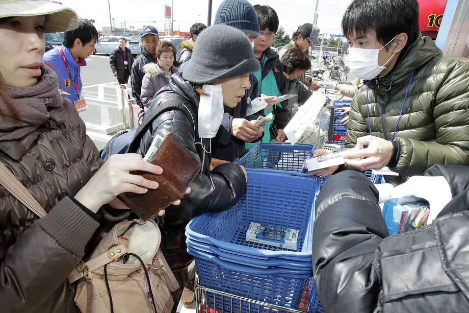 People flock around at an appliance store to buy batteries in Sendai, northern Japan, Saturday, March 12, 2011 after Japan's biggest recorded earthquake slammed into its eastern coast Friday. (AP Photo/Koji Sasahara) Photo: Koji Sasahara, ASSOCIATED PRESS / AP2011
