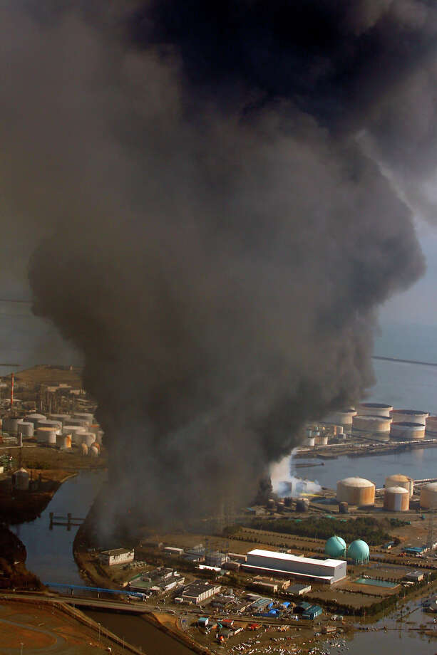 Smoke ascends over an industrial area in Sendai, northern Japan, Saturday, March 12, 2011. Japan launched a massive military rescue operation Saturday after a giant, quake-fed tsunami killed hundreds of people and turned the northeastern coast into a swampy wasteland, while authorities braced for a possible meltdown at a nuclear reactor. (AP Photo/Itsuo Inouye) Photo: Itsuo Inouye, ASSOCIATED PRESS / AP2011