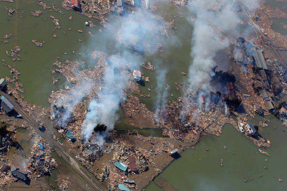 Smoke rises over an area in flood in Sendai, northern Japan, Saturday, March 12, 2011. Japan launched a massive military rescue operation Saturday after a giant, quake-fed tsunami killed hundreds of people and turned the northeastern coast into a swampy wasteland, while authorities braced for a possible meltdown at a nuclear reactor. (AP Photo/Itsuo Inouye) Photo: Itsuo Inouye, ASSOCIATED PRESS / AP2011