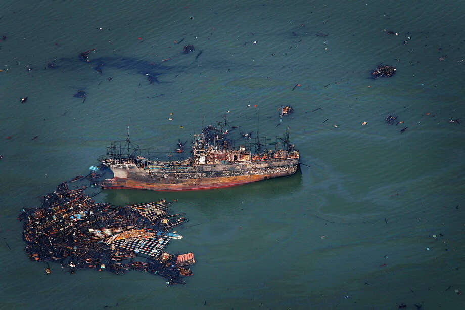 A burnt ship floats in the sea in Kesennuma, Miyagi Prefecture, Sunday, March 13, 2011 after Japan's biggest recorded earthquake hit its eastern coast Friday. (AP Photo/Itsuo Inouye) Photo: Itsuo Inouye, ASSOCIATED PRESS / AP2011