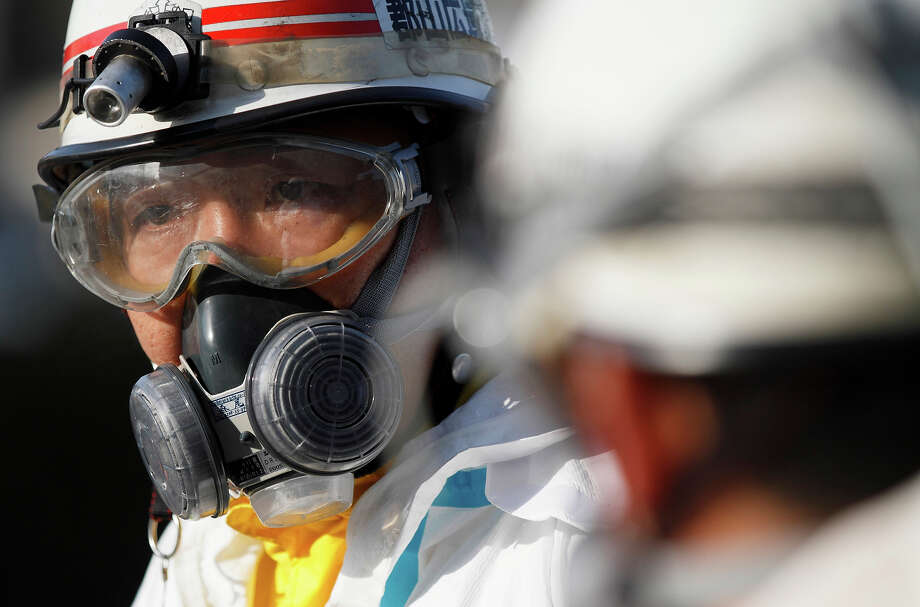 An official wears protective clothing while waiting to scan people for radiation an emergency center on Sunday, March 13, 2011, in Koriyama, northeastern Japan, two days after a giant quake and tsunami struck the country's northeastern coast.(AP Photo/Gregory Bull) Photo: Gregory Bull, ASSOCIATED PRESS / AP2011