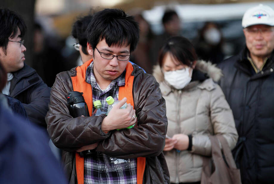 A man holds empty bottles as he waits for water an emergency center on Sunday, March 13, 2011, in Koriyama, northeastern Japan, two days after a giant quake and tsunami struck the country's northeastern coast.(AP Photo/Gregory Bull) Photo: Gregory Bull, ASSOCIATED PRESS / AP2011