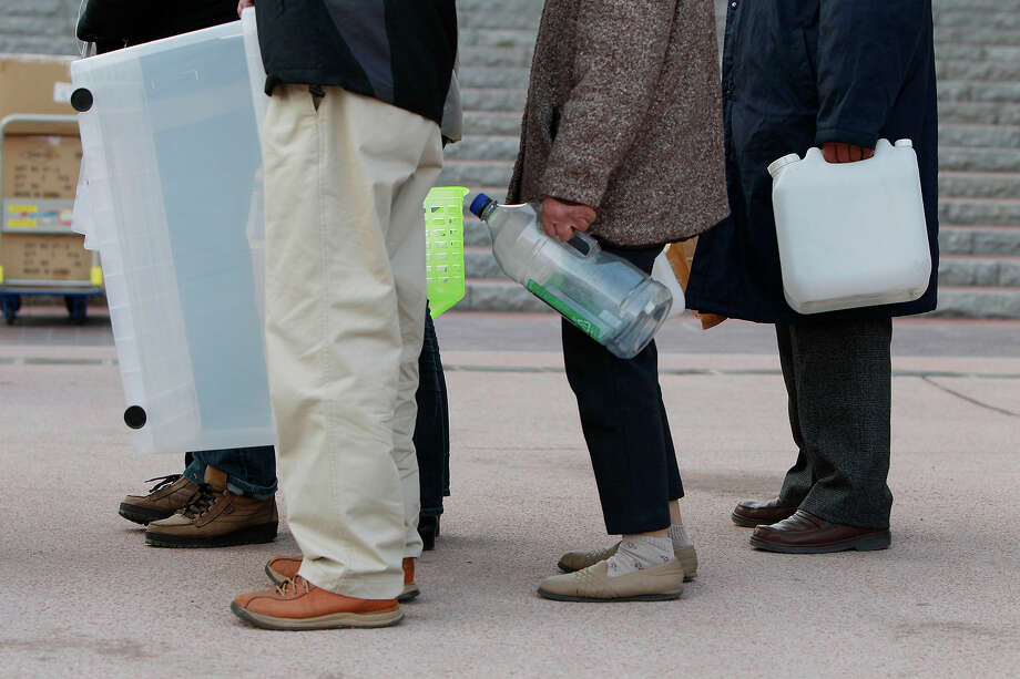 Residents queue to collect fresh water in Koriyama, Fukushima Prefecture, Japan, Sunday, March 13, 2011, two days after a giant quake and tsunami struck the country's northeastern coast. (AP Photo/Mark Baker) Photo: Mark Baker, ASSOCIATED PRESS / AP2011