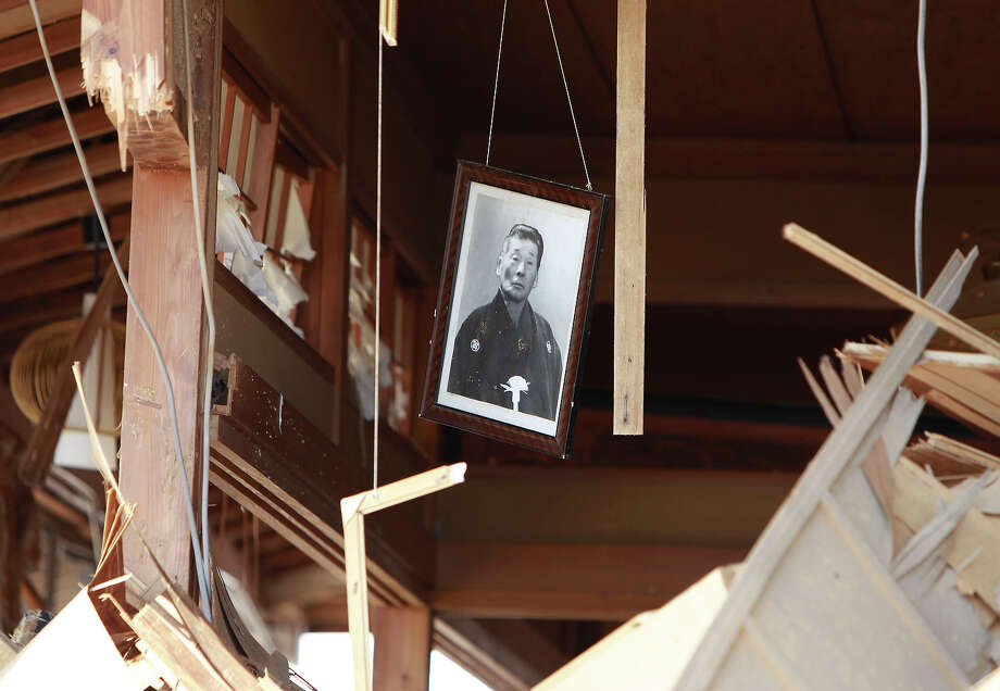 A photo hangs from the remains of a house in the seaside town of Toyoma, northern Japan, Monday, March 14, 2011, three days after a giant quake and tsunami struck the country's northeastern coast. (AP Photo/Mark Baker) Photo: Mark Baker, ASSOCIATED PRESS / AP2011