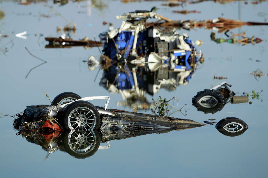 A wrecked sports car sits in flood waters, Monday, March 14, 2011, in Soma city, Fukushima prefecture, Japan, three days after a massive earthquake and tsunami struck the country's north east coast. (AP Photo/Wally Santana) Photo: Wally Santana, ASSOCIATED PRESS / AP2011