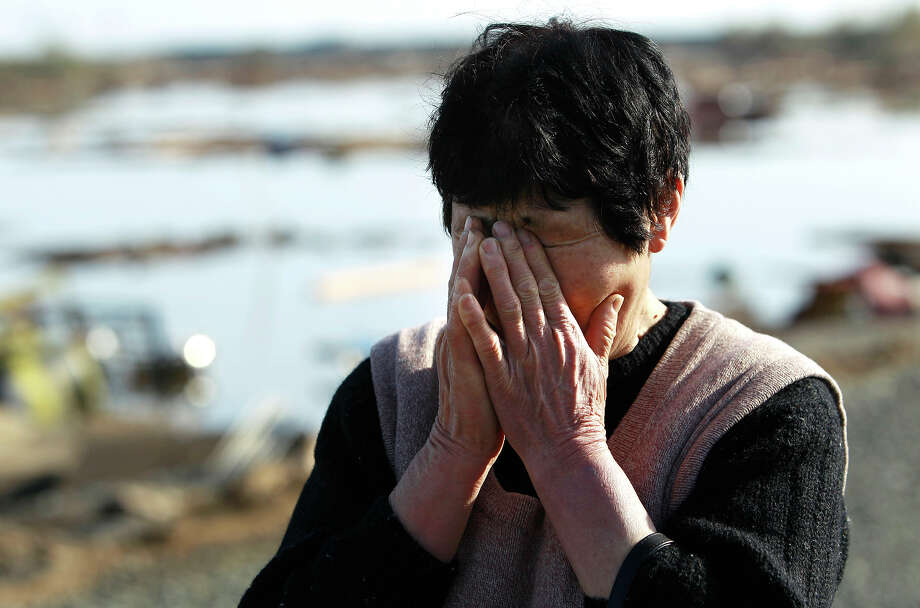A resident wipes tears as she finds no remains of her home, Monday, March 14, 2011, in Soma city, Fukushima prefecture, Japan, three days after a massive earthquake and tsunami struck the country's north east coast. (AP Photo/Wally Santana) Photo: Wally Santana, ASSOCIATED PRESS / AP2011