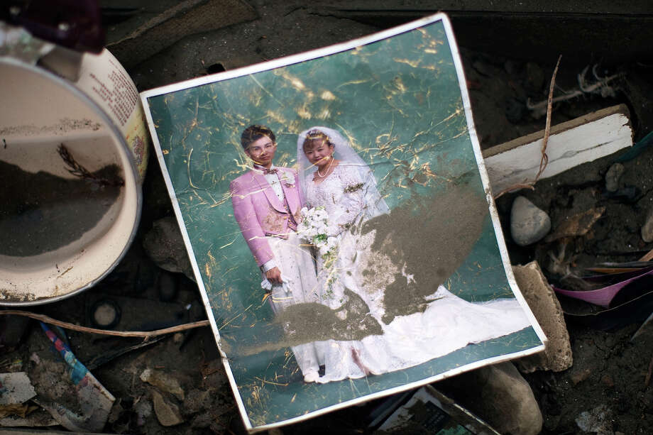 A Japanese wedding portrait lays in the rubble in the leveled city of Minamisanriku, in northeastern Japan, Tuesday March 15, 2011. (AP Photo/David Guttenfelder) Photo: David Guttenfelder, ASSOCIATED PRESS / AP2011