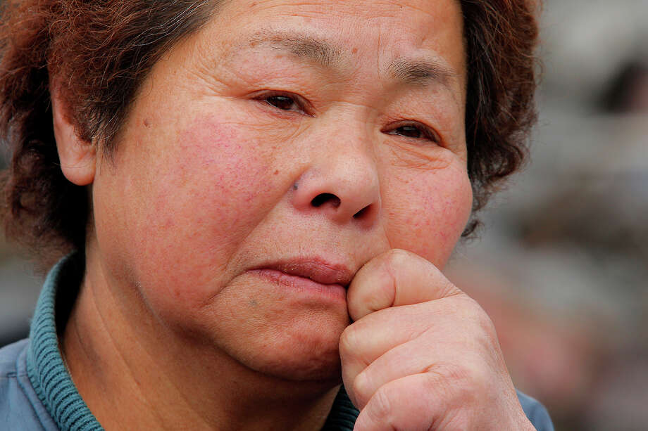 Reiko Miura, 68, cries as she looks for her sister's son at a tsunami-hit area in Otsuchi, Iwate Prefecture, northern Japan, Wednesday, March 16, 2011, after Friday's earthquake and tsunami. (AP Photo/Itsuo Inouye) Photo: Itsuo Inouye, ASSOCIATED PRESS / AP2011