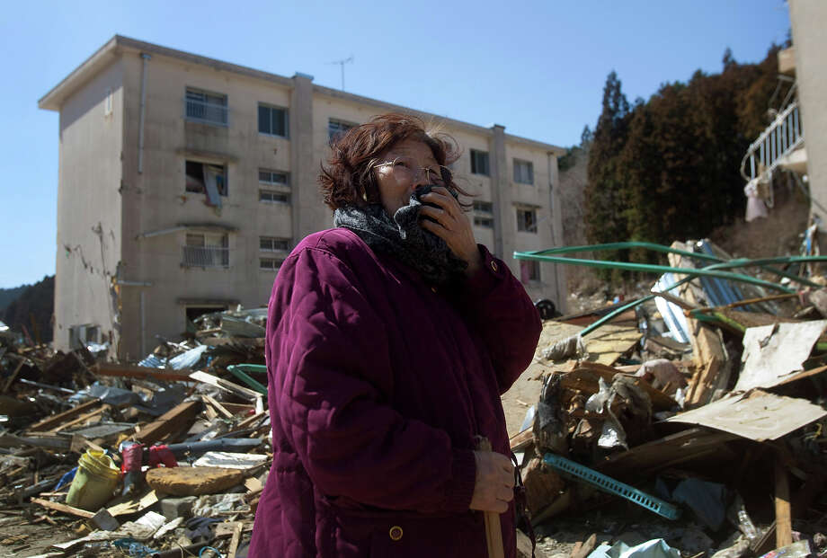 Mizue Yamamura, 76, searches the area around her damaged apartment building for her husband in Onagawa, northeastern Japan, Saturday, March 19, 2011. Yamamura said that when the tsunami approached, she and her husband began to flee for the hill behind their home but he stopped to put on his shoes and she never saw him again. (AP Photo/David Guttenfelder) Photo: David Guttenfelder, ASSOCIATED PRESS / AP2011