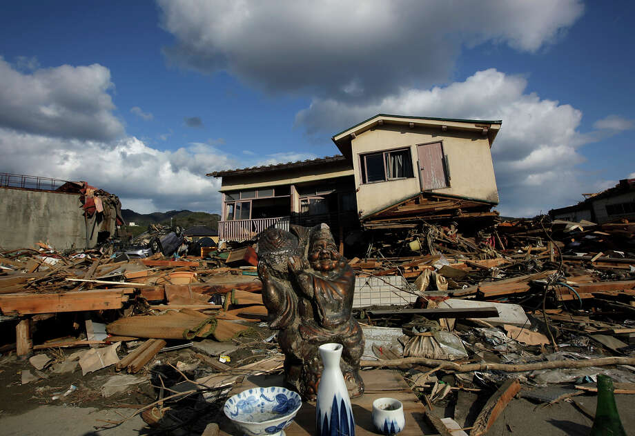 Survivors offer sake by a statue of Ebisu, the Japanese god of fishermen and one of the Seven Gods of Fortune, in front of a destroyed house in the devastated city of Kesennuma in Miyagi Prefecture Sunday, March 27, 2011 after the March 11 powerful earthquake and tsunami devastated northeastern Japan. (AP Photo/Vincent Yu) Photo: Vincent Yu, ASSOCIATED PRESS / AP2011