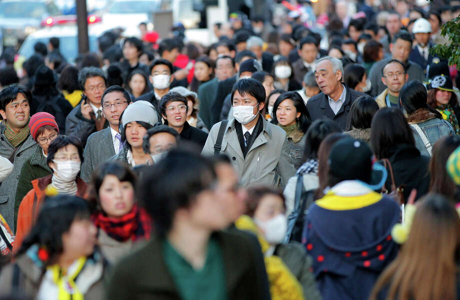 A crowd of people walk in a Tokyo street as no public transport became available after a strong earthquake hit eastern Japan Friday, March 11, 2011. (AP Photo/Itsuo Inouye) Photo: Itsuo Inouye, ASSOCIATED PRESS / AP2011