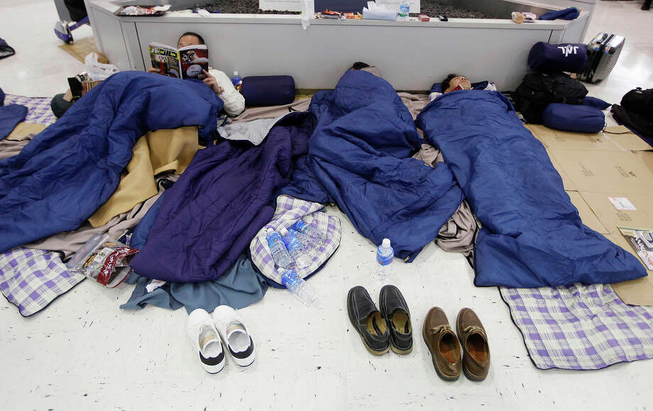 People sleep on the floor of the Narita International Airport, near Tokyo, after flights were disrupted following Friday's magnitude 8.9 earthquake on Saturday, March 12, 2011. Japan launched a massive military rescue operation Saturday after a giant, quake-fed tsunami killed hundreds of people and turned the northeastern coast into a swampy wasteland, while authorities braced for a possible meltdown at a nuclear reactor. (AP Photo/Mark Baker) Photo: Mark Baker, ASSOCIATED PRESS / AP2011