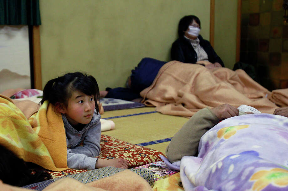 A young girl watches the news in a community center after being evacuated from areas surrounding the Fukushima nuclear facilities following Friday's massive 8.9 earthquake, in Iwaki City, Fukushima prefecture, Japan, Saturday, March 12, 2011. (AP Photo/Wally Santana) Photo: Wally Santana, ASSOCIATED PRESS / AP2011