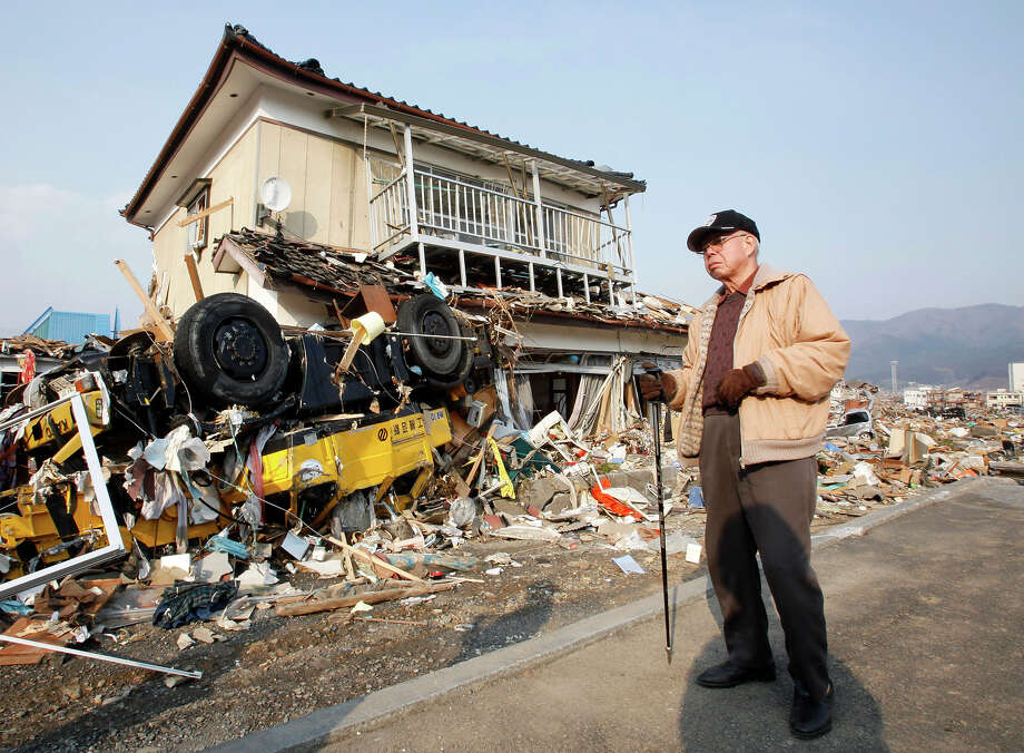 A man stands near a damaged house in Ofunato, Iwate Prefecture, northern Japan, Sunday, March 13, 2011, two days after a powerful earthquake-triggered tsunami hit Japan's east coast. (AP Photo/Shizuo Kambayashi) Photo: Shizuo Kambayashi, ASSOCIATED PRESS / AP2011