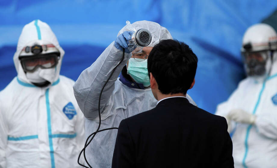 An official scans a man for radiation at an emergency center Sunday, March 13, 2011, in Koriyama, northeastern Japan, two days after a giant quake and tsunami struck the country's northeastern coast.(AP Photo/Gregory Bull) Photo: Gregory Bull, ASSOCIATED PRESS / AP2011