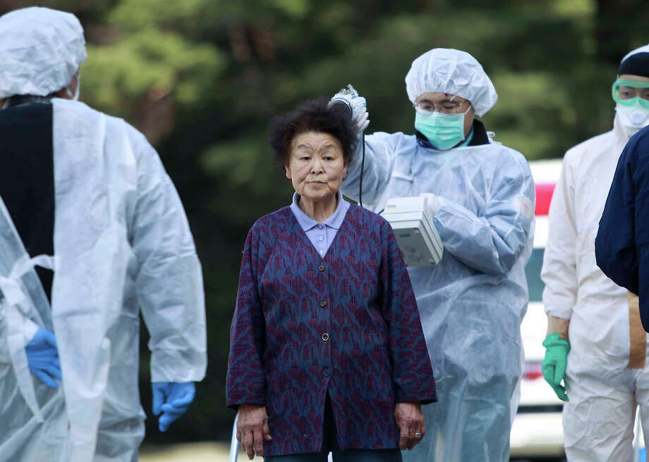Residents evacuated from areas surrounding the Fukushima nuclear facilities damaged in Friday's massive earthquake, are checked for radiation contamination, Sunday, March 13, 2011, in Koriyama city, Fukushima prefecture, Japan. (AP Photo/Wally Santana) Photo: Wally Santana, ASSOCIATED PRESS / AP2011