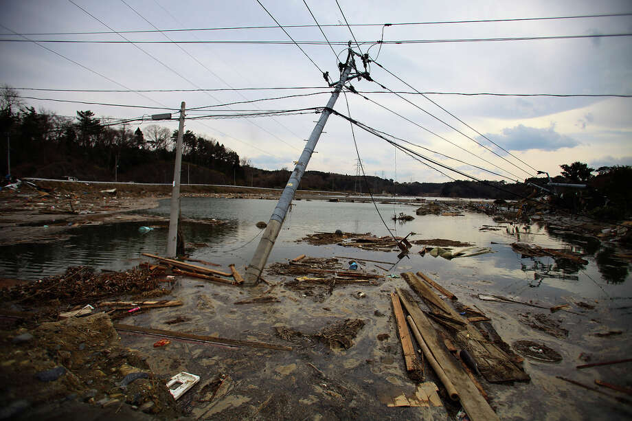 Leaning electric poles are left in the area following massive tsunami triggered by March 11 earthquake in Daigasaki, near Sendai, Miyagi Prefecture, Japan, Monday, March 14, 2011. (AP Photo/Junji Kurokawa) Photo: Junji Kurokawa, ASSOCIATED PRESS / AP2011