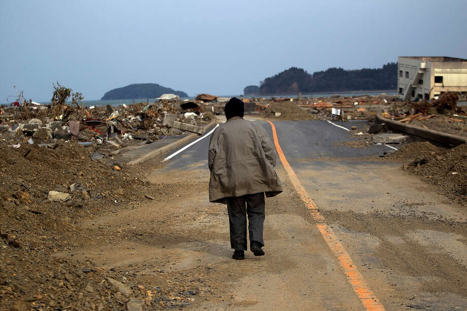 A Japanese earthquake and tsunami survivor walks alone on a road past the destroyed village of Saito, in northeastern Japan, Monday, March 14, 2011. (AP Photo/David Guttenfelder) Photo: David Guttenfelder, ASSOCIATED PRESS / AP2011