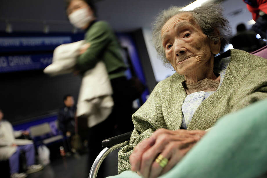 An elderly evacuee from Futaba, a town near the tsunami-crippled Fukushima Dai-ichi nuclear plant in Fukushima Prefecture, arrives at her new evacuation shelter at Saitama Super Arena in Saitama, northern Tokyo, Saturday, March 19, 2011. (AP Photo/Eugene Hoshiko) Photo: Eugene Hoshiko, ASSOCIATED PRESS / AP2011