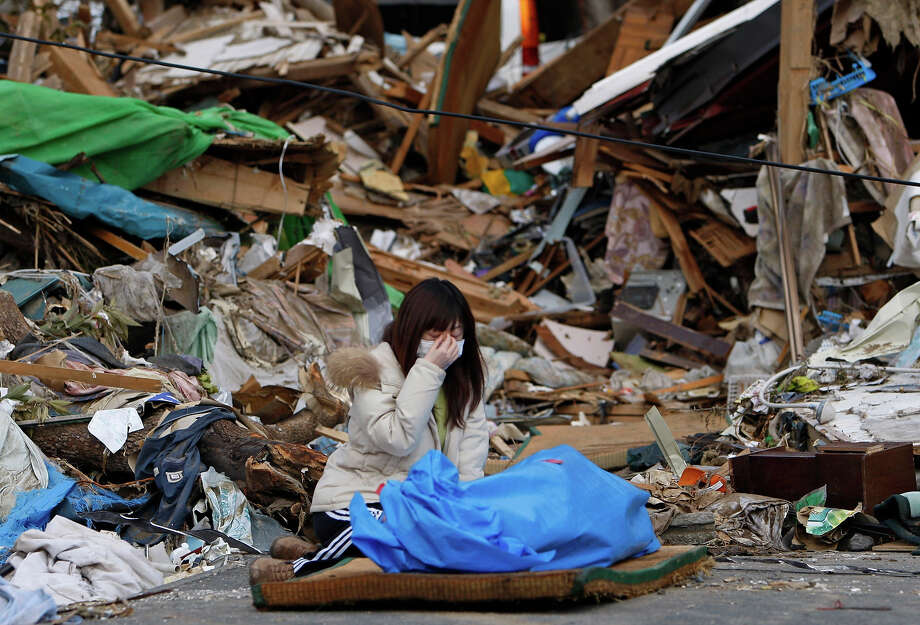 Tayo Kitamura, 40, kneels in the street to caress and talk to the wrapped body of her mother Kuniko Kitamura, 69, after Japanese firemen discovered the dead woman inside the ruins of her home in Onagawa, northeastern Japan, Saturday, March 19, 2011, following the last week's earthquake and tsunami. (AP Photo/Shuji Kajiyama) Photo: Shuji Kajiyama, ASSOCIATED PRESS / AP2011
