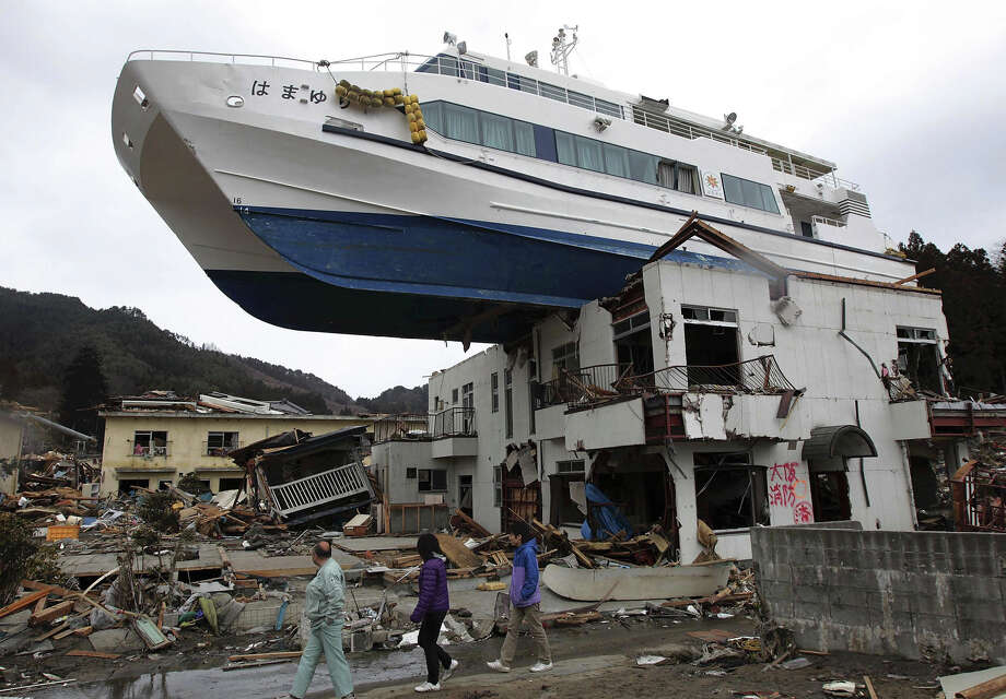 FOR USE AS DESIRED, YEAR END PHOTOS - FILE -In this March 22, 2011 file photo, a boat sits atop a building in Otsuchi, Iwate Prefecture, Japan, following the March 11 earthquake and tsunami which devastated a vast area of northeastern Pacific coast of Japan. (AP Photo/Yomiuri Shimbun, File) JAPAN OUT, MANDATORY CREDIT Photo: Hiroto Nomoto, ASSOCIATED PRESS / AP2011